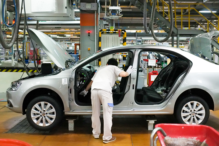 a worker in an Automotive assembly line inspecting car