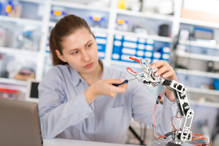Young woman building Robotics in a lab